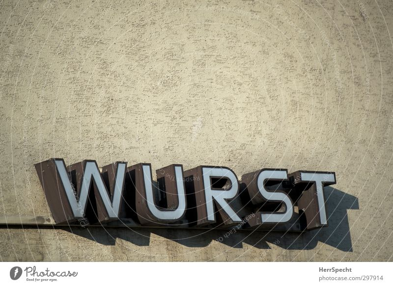 It's everything anyway... Town Building Wall (barrier) Wall (building) Stone Metal Characters Gloomy Brown Butcher Sausage Store premises Neon sign Beige