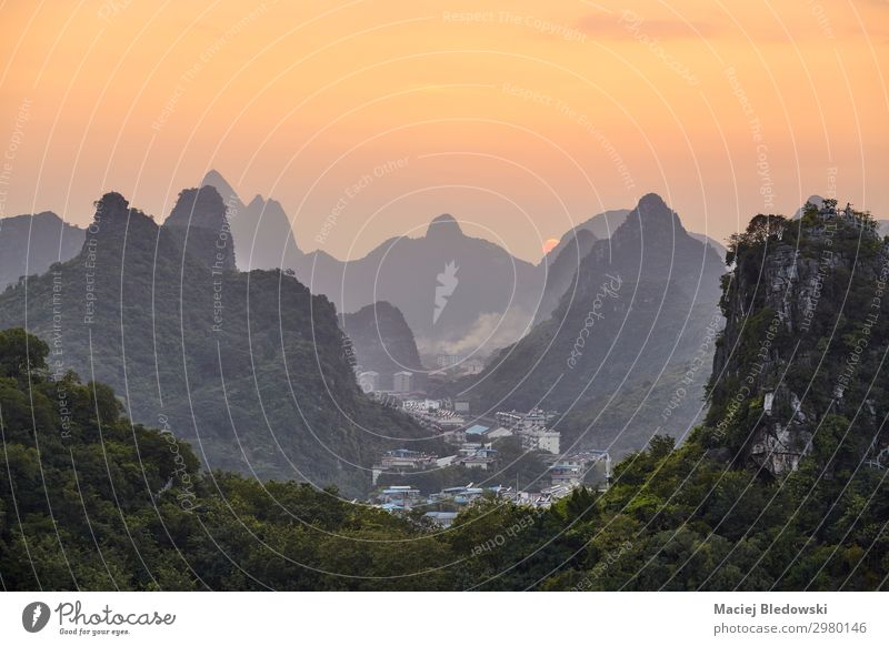 Scenic sunset over Karst mountains in Guilin, China. Beautiful Vacation & Travel Tourism Trip Adventure Sightseeing Sun Mountain Hiking Nature Landscape Fog