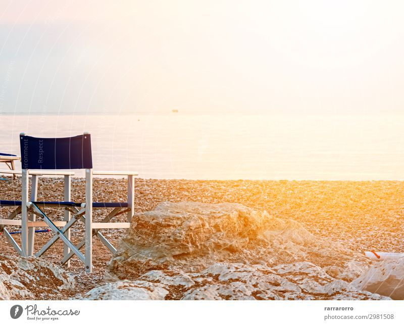 empty folding outdoor chair on a pebble beach Relaxation Leisure and hobbies Vacation & Travel Tourism Summer Sun Beach Ocean Chair Nature Landscape Sand Sky