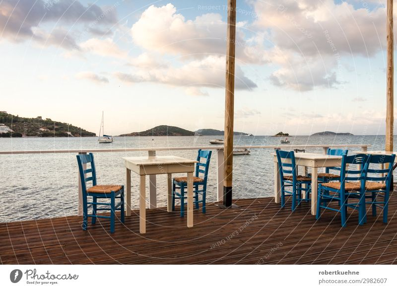 Empty tables in a restaurant by the sea Vacation & Travel Tourism City trip Summer Summer vacation Ocean Island Chair Table Restaurant Services Gastronomy Sky