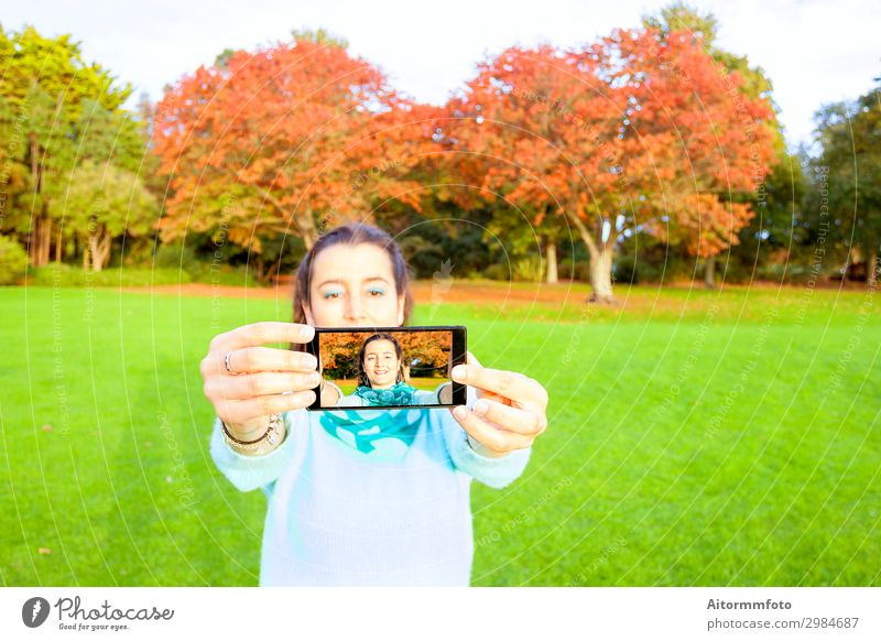 Woman taking selfie Lifestyle Happy Beautiful Vacation & Travel Telephone PDA Camera Internet Human being Adults Nature Autumn Park Fashion Smiling Happiness