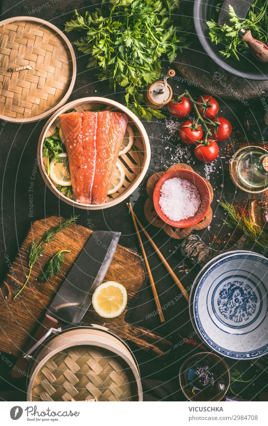 Authentic asian food cooking preparation with salmon,seasoning, spices, bowls and chopsticks on dark kitchen table, top view. Various ingredients, utensils and tools on kitchen table.  Asian cuisine