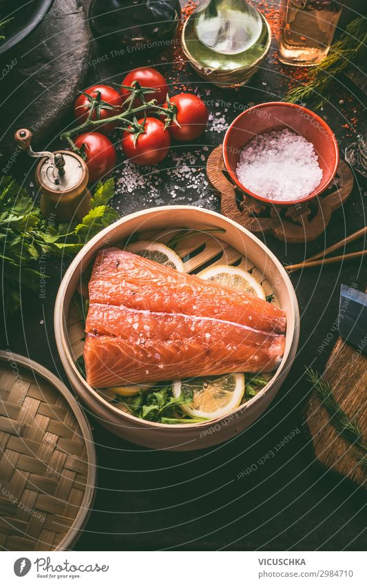Raw salmon fillet in bamboo steamer on dark rustic kitchen table with fresh ingredients and tools. Healthy eating and cooking. Dieting concept. Asian cuisine. Cooking preparation