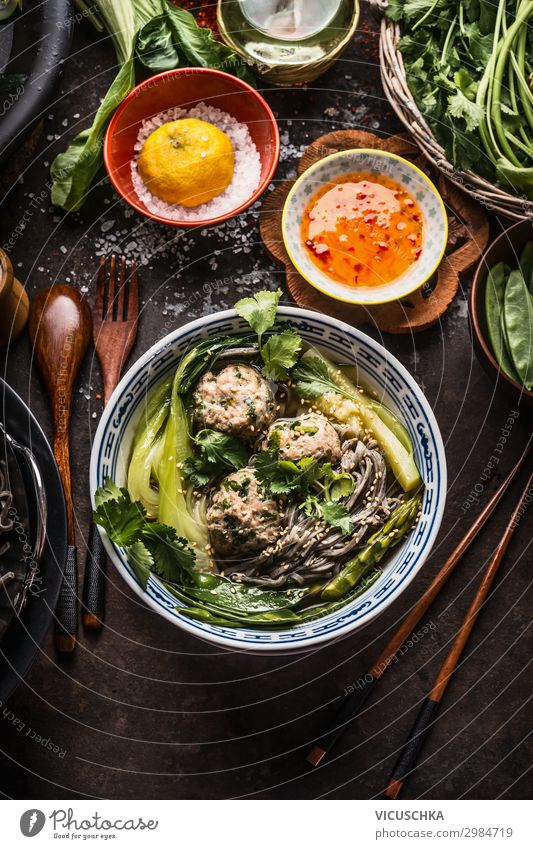 Asian noodles bowl with green vegetables, bok choy and meat balls on dark background with wooden cutlery, chopsticks and hot sauce, top view. Close up. Healthy asian meal. Asian cuisine concept