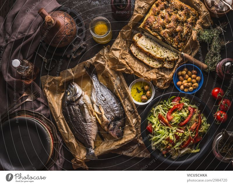 Mediterranean lunch or dinner with roasted dorado fishes, homemade focaccia bread , olive oil and olives served on rustic table with tableware and kitchen utensils, top view.
