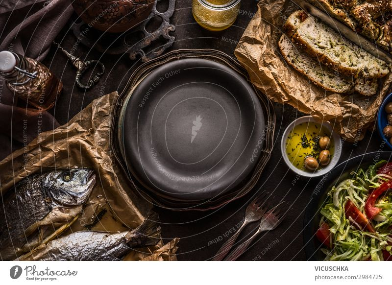 Food background of  Mediterranean food with Focaccia bread , roasted dorado fishes, salad bowl and olives oil on dark rustic kitchen table around empty plate. Delicious Mediterranean  cuisine concept.