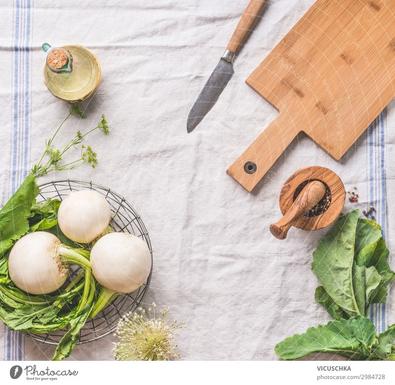 Food background with raw young turnip  with greens on light kitchen table with cutting board and knife, top view. Healthy vegetarian eating and cooking concept. Copy space for your design