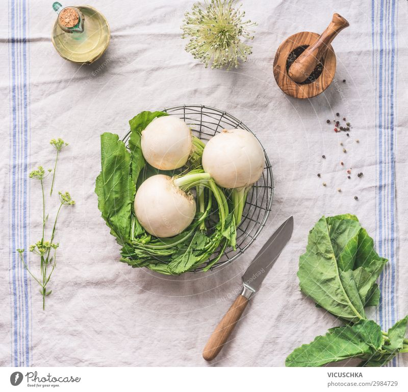 Raw young turnip  with greens on light kitchen table with knife, top view. Healthy vegetarian eating and cooking concept raw healthy green foods green colors