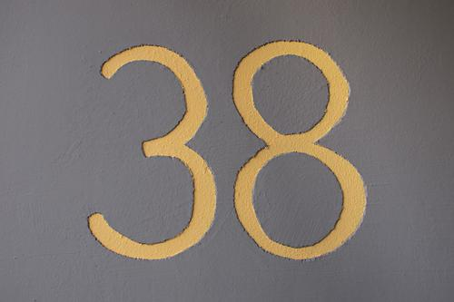 yellow number 38 on grey wall - house number thirty-eight Wall (barrier) Wall (building) Yellow Gray Symbols and metaphors Digits and numbers House number