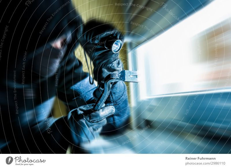 A burglar with a crowbar and a flashlight looks through a window Human being 1 Detached house Window Observe Looking Wait Dark Blue Animosity Aggression Force