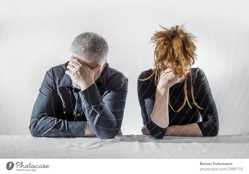 A man and a woman sit at a table, they seem depressed and silent Human being Masculine Feminine Woman Adults Man 2 Sit Argument Sadness Wait Emotions Grief