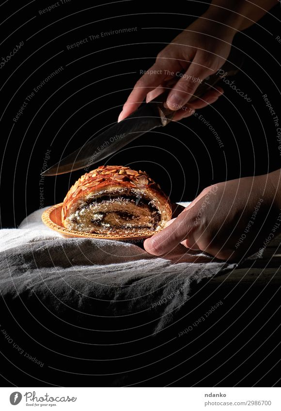 female hands cut baked roll with poppy seeds Dough Baked goods Bread Dessert Knives Body Table Woman Adults Hand Wood Eating Dark Fresh Delicious Natural Brown