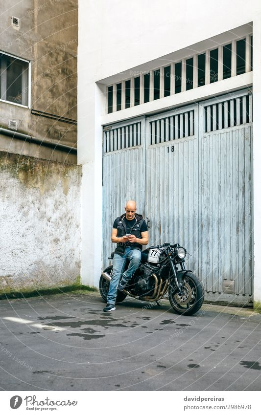 Biker looking mobile sitting on motorcycle Lifestyle Style Trip PDA Engines Human being Man Adults Street Vehicle Motorcycle Sit Wait Authentic Retro Black