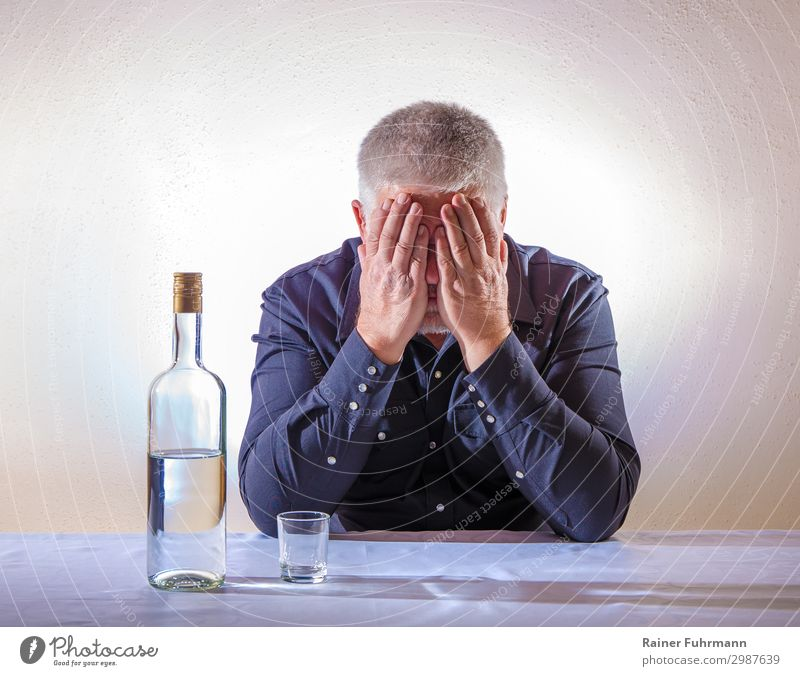 A man sits at a table and covers his face with his hands. On the table is a bottle of alcohol and an empty shot glass Man Alcoholic drinks vodka Alcoholics