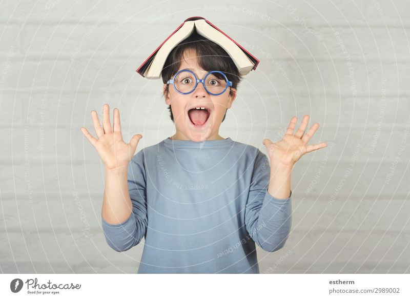 happy and smiling child with book on head Lifestyle Joy Playing Reading Child School Schoolchild Human being Masculine Boy (child) Infancy 1 8 - 13 years Book