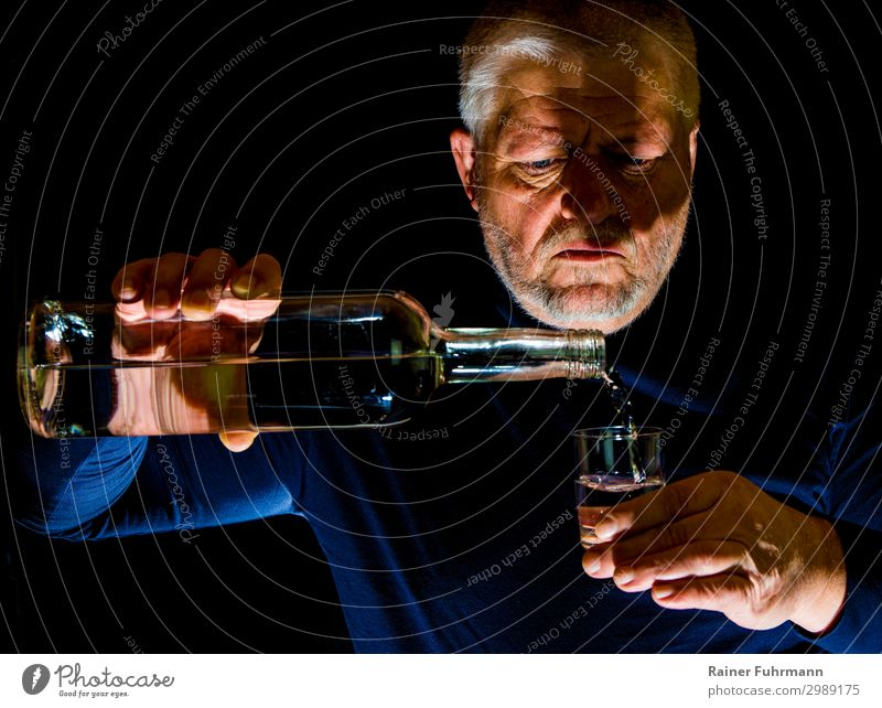 "A man pours alcohol into a glass Human being Masculine Man Adults 1 Gray-haired ""Bottle Glass Schnaps glass Alcohol"" Drinking Alcoholism Addiction ""Alcoholism"
