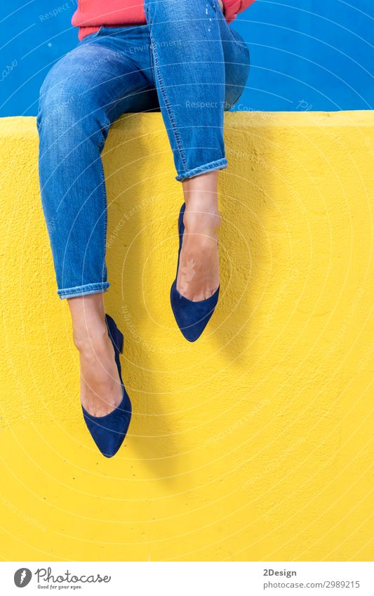 Closeup view of woman heels on a yellow wall Lifestyle Style Beautiful Relaxation Summer Human being Woman Adults Feet Warmth Fashion Jeans Footwear High heels