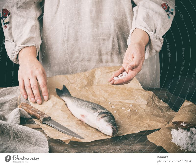 fresh whole sea bass fish lying on brown paper Meat Fish Seafood Herbs and spices Nutrition Ocean Table Kitchen Tool Human being Hand Animal Paper Wood Make