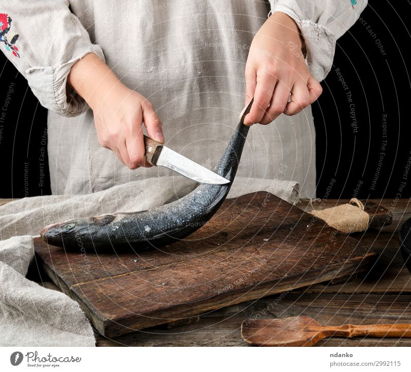 woman in gray linen clothes cleans the fish sea bass Fish Seafood Knives Table Kitchen Tool Woman Adults Hand Fingers Wood Old Make Fresh Clean Brown Gray Black