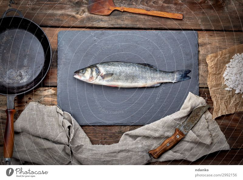 fresh whole sea bass fish on a black board Meat Seafood Nutrition Dinner Pan Knives Table Kitchen Gastronomy Tool Nature Animal Wood Old Make Fresh Natural
