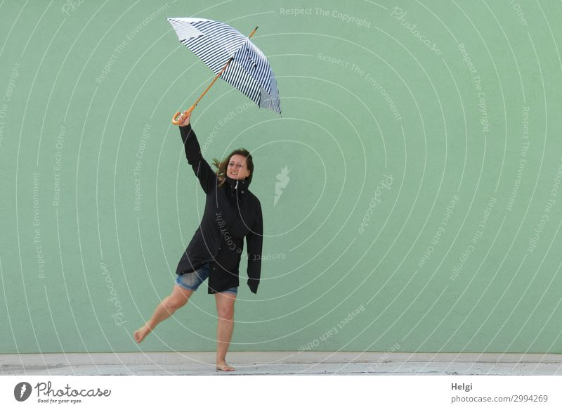 Woman with dark jacket and short jeans stands barefoot on one leg in front of a light green wall and holds up an umbrella Human being Feminine Adults 1