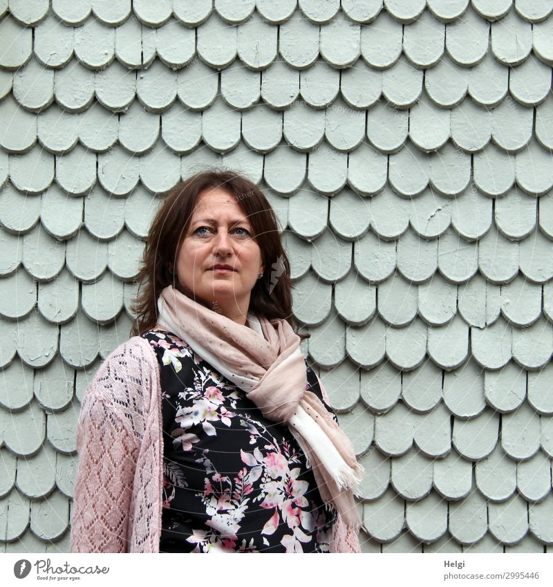 Woman with dark long hair, colourful dress, pink cardigan and pink scarf is standing in front of a grey wall of wooden shingles Human being Feminine Adults 1