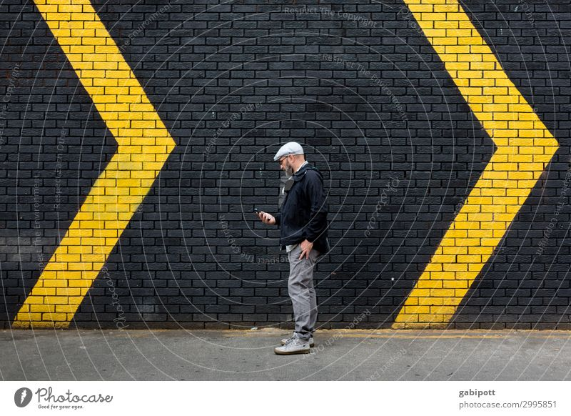 Man in front of a black wall with yellow arrows Human being Masculine Adults 1 Wall (barrier) Wall (building) Facade Sign Signs and labeling Signage