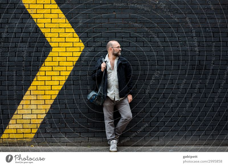 Man in front of a black wall with yellow arrows Human being Masculine Adults 1 Yellow Black Wall (building) Arrow Signs and labeling Right Left Movement