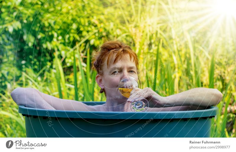 In high temperatures and sunshine in summer, a woman bathes in a rain barrel. In her hand she holds a glass of white wine. Human being Feminine Woman Adults
