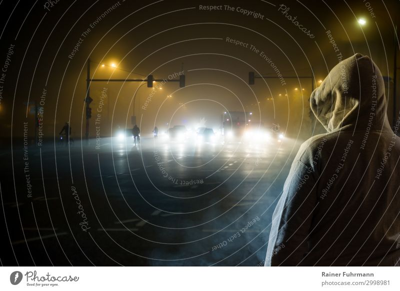 "a man watches the traffic at night Human being Man Adults 1 Fog Town Capital city Populated ""street Avenue Main Street"" Transport Traffic infrastructure"