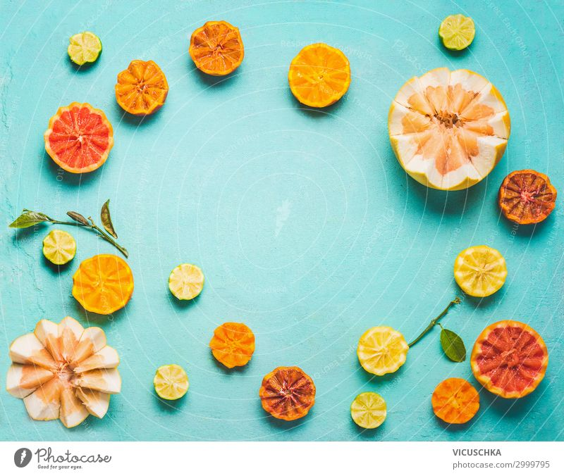 Frame of various colorful citrus fruits halves with green leaves on light blue background, top view. Copy space for your design. Flat lay. Healthy food ad lifestyle concept. Source of vitamin C