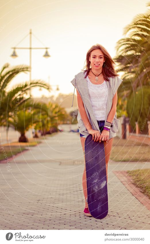 Young girl with a skateboard outdoors on summer Woman Human being Youth (Young adults) Summer Beautiful Tree Joy Street Lifestyle Adults Warmth Sports Happy