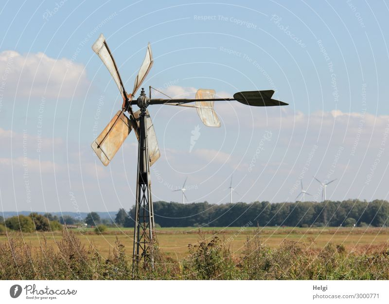 small historical windmill made of metal stands on a meadow, in the distance modern wind turbines Technology Energy industry Renewable energy Wind energy plant