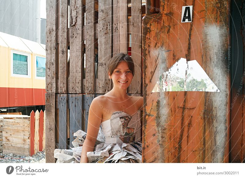 Young woman in a newspaper dress in front of a wooden wall. Feminine Youth (Young adults) Adults Truth Media Newspaper Print shop Magazine Art Body art