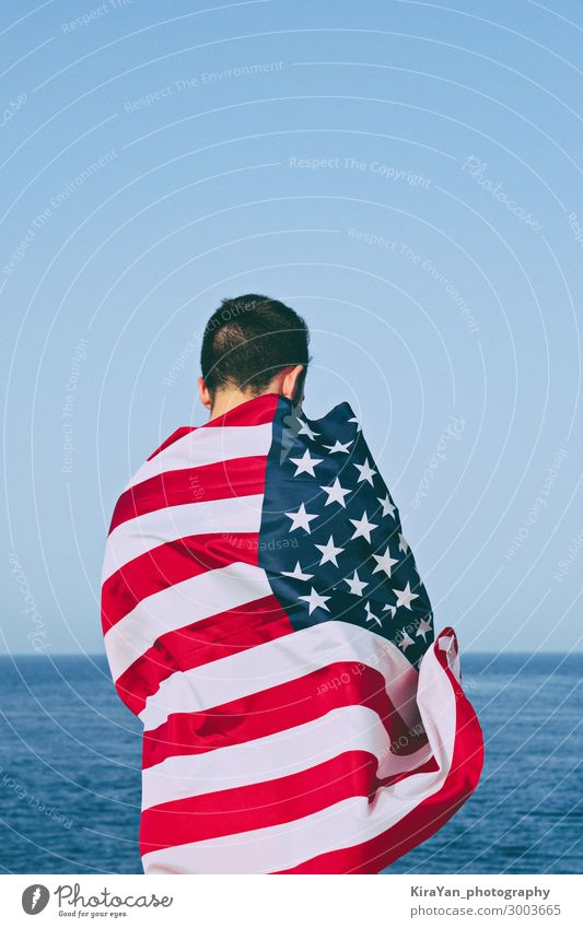Man from behind wrapped in American Flag against blue sky Happy Freedom Ocean Feasts & Celebrations Adults Hand Sky Monument Stripe Blue Honor Independence