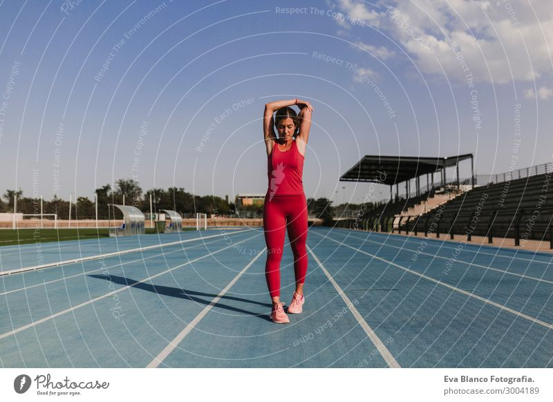 fitness woman runner stretching arms on stadium. Healthy life Woman Human being Sky Youth (Young adults) Young woman Summer Blue Town Beautiful Green White Red