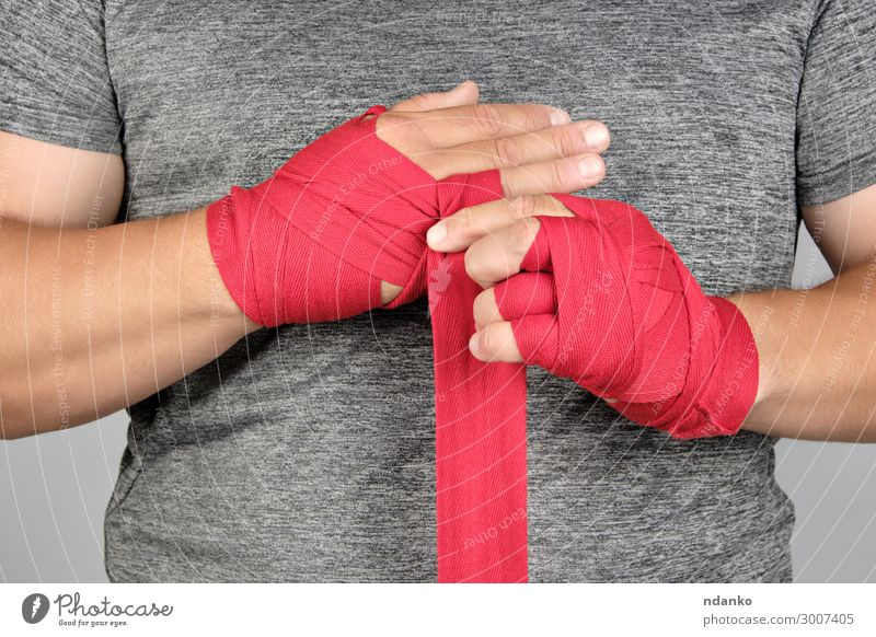 sportsman's hands wrapped in a red elastic sports bandage Lifestyle Body Athletic Fitness Sports Human being Masculine Man Adults Hand Movement Stand Aggression