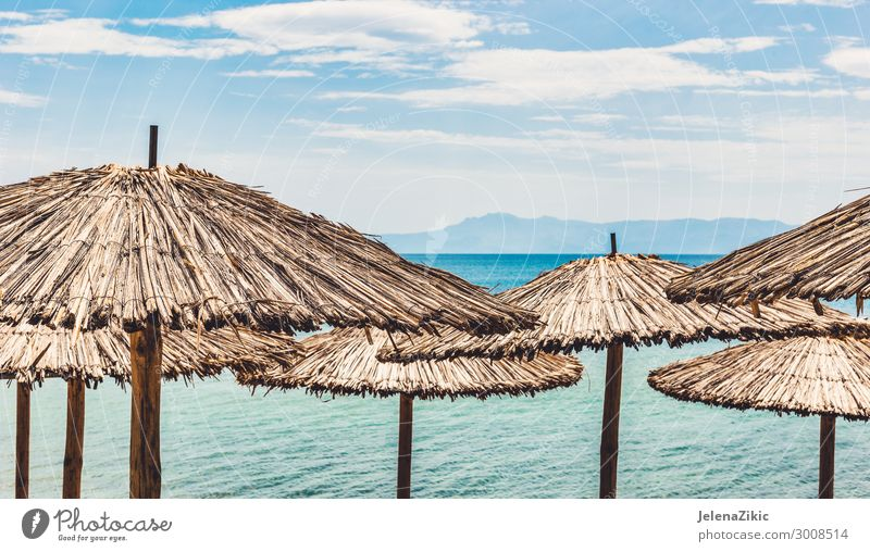 Straw umbrellas on tropical beach Sky Vacation & Travel Nature Summer Beautiful Water Landscape Sun Ocean Relaxation Clouds Beach Wood Coast Tourism Copy Space