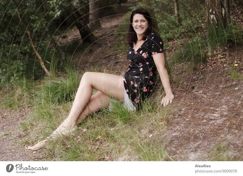 Portrait of a tall young woman sitting smiling in a clearing Lifestyle Joy luck already Young woman Youth (Young adults) Legs 18 - 30 years Adults Nature Plant