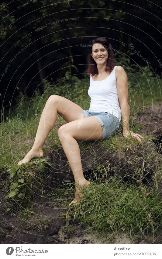 Portrait of a tall young woman on a fragile lake shore in front of a forest Lifestyle Joy luck already Relaxation Young woman Youth (Young adults) Legs