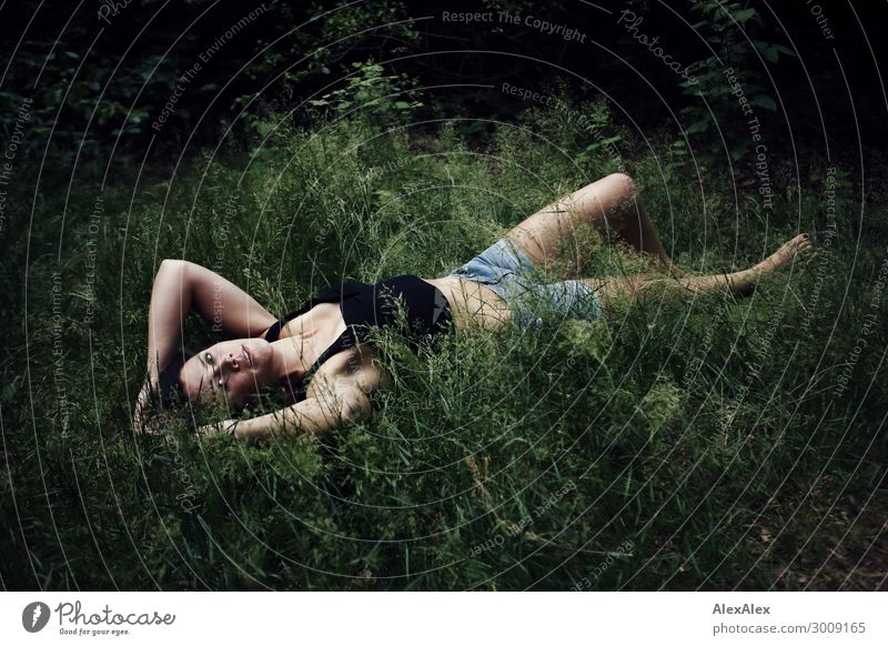 Portrait of a tall young woman lying in deep grass Lifestyle Joy luck already Well-being Senses Young woman Youth (Young adults) 18 - 30 years Adults Nature