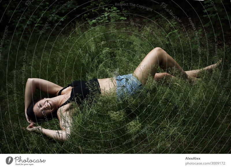 Portrait of a tall young woman lying in the grass and smiling Lifestyle Joy luck already Well-being Young woman Youth (Young adults) 18 - 30 years Adults Nature