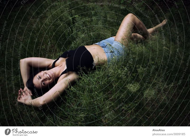 Young woman lies in dark forest in the grass Lifestyle Joy Happy Beautiful Well-being Youth (Young adults) 18 - 30 years Adults Nature Landscape Plant