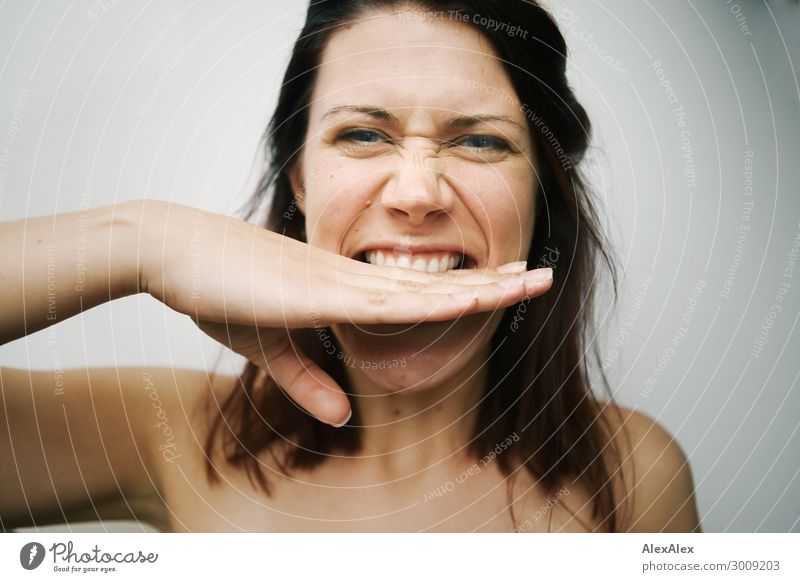 Close portrait of a young woman biting her hand in front of a white wall Lifestyle Joy already Young woman Youth (Young adults) Face by hand 18 - 30 years
