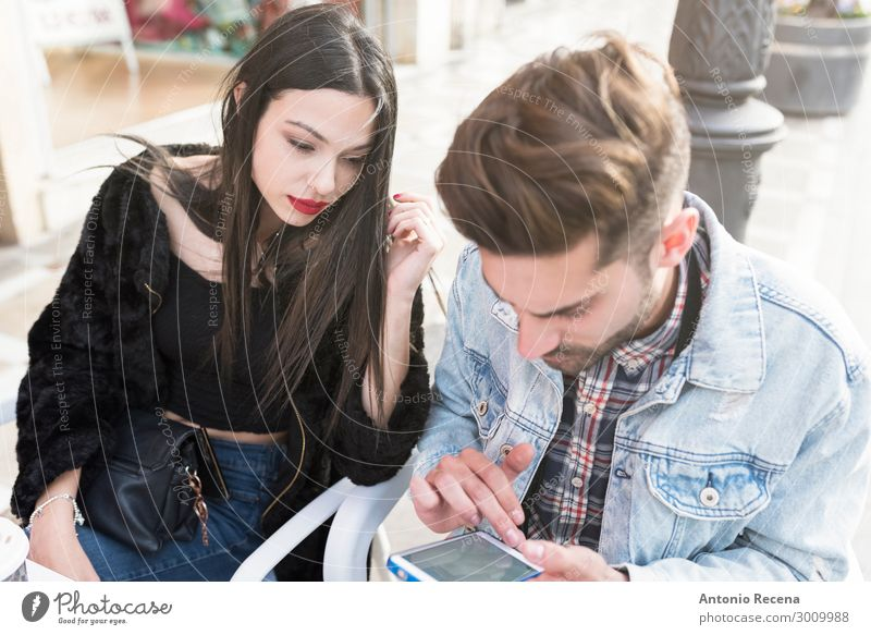 Young couple looking smartphone in bar terrace Coffee Lifestyle Telephone PDA Internet Human being Woman Adults Man Couple Terrace Fashion Eroticism Together