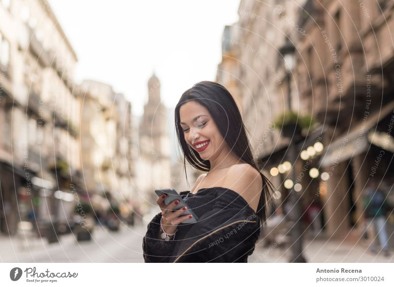 Young woman looking smartphone in afternoon image Lifestyle Telephone PDA Technology Internet Human being Woman Adults Brunette Smiling communication City young