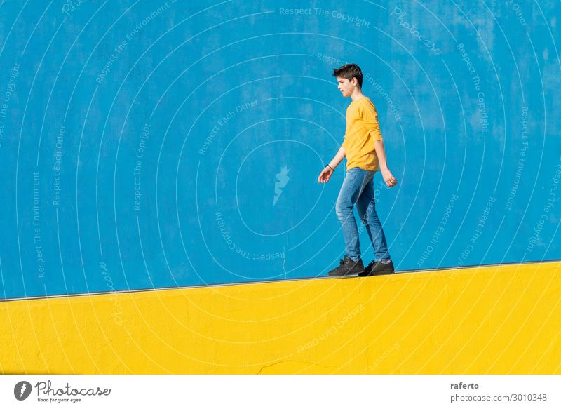 Young boy wearing casual clothes walking against a blue wall Lifestyle Summer Sun Human being Masculine Child Boy (child) Man Adults Youth (Young adults) 1