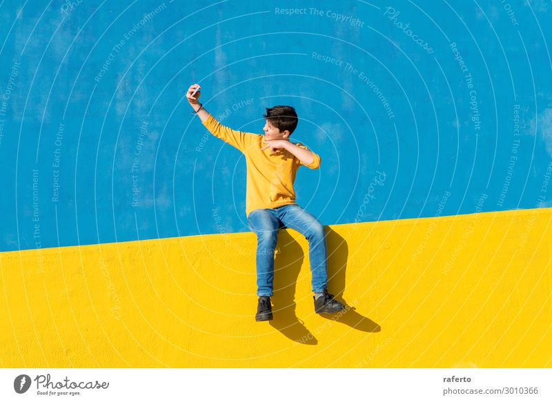 Front view of a young boy wearing casual clothes sitting on a yellow fence against a blue wall while using a mobile phone Lifestyle Summer Telephone Cellphone
