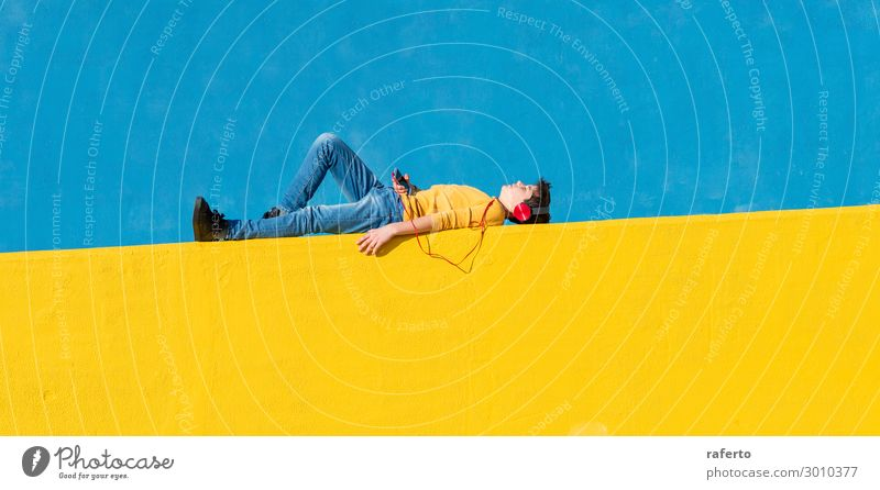 Front view of a young boy wearing casual clothes lying on a yellow fence against a blue wall while using a mobile phone to listening music Lifestyle Music