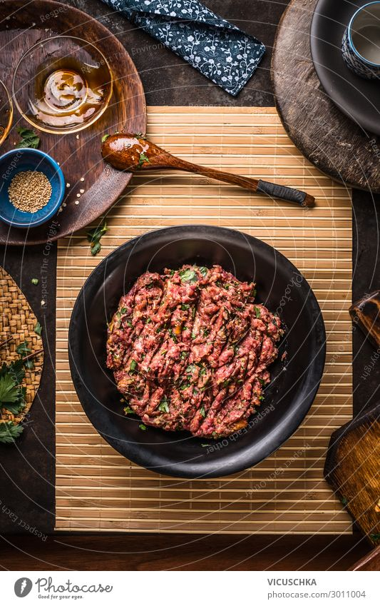 Meat stuffing in black bowl on dark rustic kitchen table with bowls and plates, top view meat concept minced meat ground meat above over recipes grinder